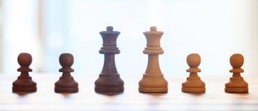Pezzi degli scacchi scuri, colore marrone chiaro Vista del primo piano delle regine e dei pegni con i dettagli Contesto della sfu Fotografie Stock Libere da Diritti