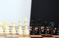 pezzi degli scacchi su un bianco laterale del supporto sull'altro nero immagine stock