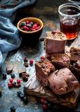 Pezzi del brownie con le bacche su fondo blu scuro immagini stock libere da diritti