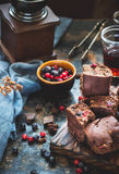 Pezzi del brownie con le bacche su fondo blu scuro fotografie stock
