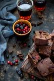 Pezzi del brownie con le bacche su fondo blu scuro fotografia stock libera da diritti