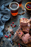Pezzi del brownie con le bacche su fondo blu scuro fotografie stock libere da diritti