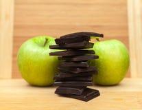 Pezzi del cioccolato con le mele sulla Tabella Immagini Stock