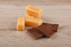 Pezzi del cioccolato e caramelle del caramello sul fondo di legno della tavola Fotografie Stock Libere da Diritti