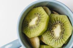 Pezzi del kiwi su una ciotola blu Fotografie Stock