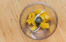 Pezzi del mango in tazza del miscelatore sulla Tabella di legno Immagini Stock Libere da Diritti