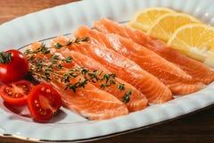 Pezzi del pesce dell'aringa con il limone, cipolla immagini stock