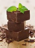 Pezzi del primo piano di parti del cioccolato e di foglie di menta sul BAC di legno fotografia stock