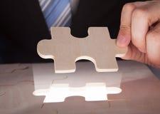 Pezzi del puzzle della riparazione dell'uomo d'affari allo scrittorio Fotografia Stock Libera da Diritti