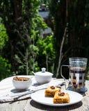 Pezzi di baklava dolce sul piatto, fondo verde del giardino Fotografia Stock