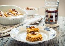 Pezzi di baklava dolce sul piatto, fondo verde del giardino Immagini Stock