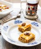 Pezzi di baklava dolce sul piatto, fondo verde del giardino Immagine Stock Libera da Diritti