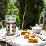 Pezzi di baklava dolce sul piatto, fondo verde del giardino Fotografie Stock