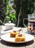 Pezzi di baklava dolce sul piatto, fondo verde del giardino Immagine Stock