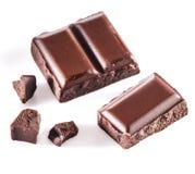Pezzi di barra di cioccolato su un fondo bianco Fotografie Stock