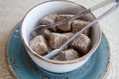 Pezzi di bianco e di zucchero bruno in una ciotola con le tenaglie per zucchero immagini stock libere da diritti