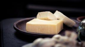 Pezzi di burro sul piatto con fondo scuro Immagine Stock Libera da Diritti