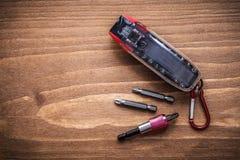 Pezzi di cacciavite intercambiabili in contenitore sul bordo di legno Fotografia Stock