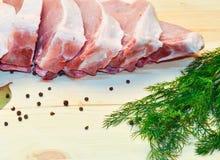 Pezzi di carne suina su fondo di legno accanto a pepe ed alla foglia di alloro, verde dell'aneto Immagine Stock Libera da Diritti