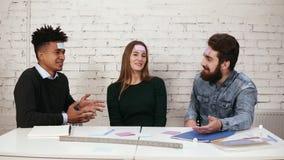 Pezzi di carta dei giovani incollati sulle parole di congettura e della fronte Società degli amici divertendosi nell'ufficio vari archivi video