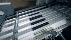 Pezzi di carta stanno muovendo velocemente attraverso il torchio tipografico archivi video