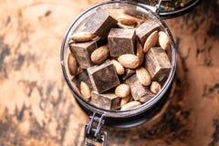 Pezzi di cioccolato amaro scuro con cacao e le mandorle matte su fondo di legno Concetto degli ingredienti della confetteria fotografie stock libere da diritti