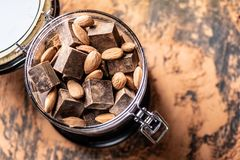 Pezzi di cioccolato amaro scuro con cacao e le mandorle matte su fondo di legno Concetto degli ingredienti della confetteria fotografia stock libera da diritti