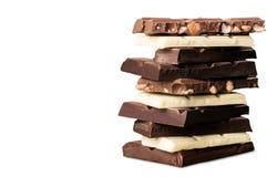 Pezzi di cioccolato delizioso su fondo bianco Immagini Stock