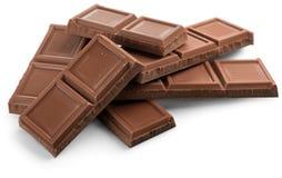 Pezzi di cioccolato delizioso su fondo bianco Fotografia Stock