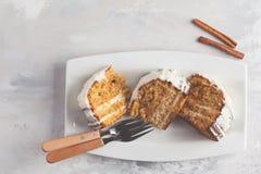 Pezzi di dolce alle carote casalingo con crema bianca su un piatto bianco, Fotografia Stock