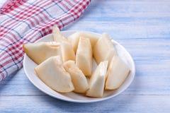 Pezzi di melone fresco su un piatto bianco su una tavola di legno blu immagine stock libera da diritti