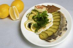 Pezzi di pesce, uova, pane, cetrioli, limone vicino agli spuntini freddi immagine stock
