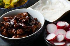 Pezzi di pollo di teriyaki, di vermicelli del riso e di ravanello sul primo piano della tavola Cucina asiatica Fotografie Stock