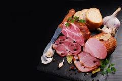 Pezzi di prosciutto affumicato casalingo della carne di maiale su fondo e su spazio neri Fotografia Stock