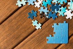Pezzi di puzzle differenti su una tavola di legno Il concetto di Th Fotografia Stock Libera da Diritti