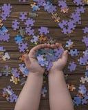 Pezzi di puzzle nelle mani di un bambino Fotografie Stock Libere da Diritti