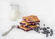 Pezzi di torta di mirtillo sulla carta bianca di cottura Fotografia Stock Libera da Diritti