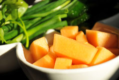 Pezzi di zucca su un piatto bianco con i verdi Fotografia Stock