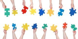 Pezzi differenti stabiliti di puzzle in mani della gente Fotografia Stock