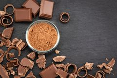 Pezzi e cacao in polvere rotti del cioccolato su un fondo scuro Vista superiore con copyspace per il vostro testo immagine stock libera da diritti