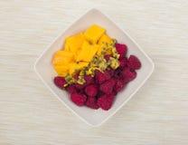 Pezzi e lamponi del mango con frutto della passione in una ciotola bianca sul fondo beige del tessuto Fotografia Stock Libera da Diritti