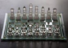 Pezzi e scacchiera di vetro Immagini Stock