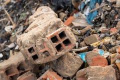 Pezzi rotti di parete concreta del cemento con i mattoni in rottamaio - mucchio dei rifiuti dell'immondizia della costruzione - s fotografia stock