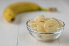 Pezzi tagliati di banana in una ciotola di vetro su una tavola di legno fotografia stock libera da diritti