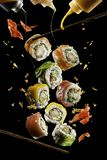 Pezzi volanti di sushi con i bastoncini e la salsa di legno, isolati su fondo nero Alimento di volo e concetto di moto fotografie stock
