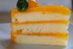 Pezzo del primo piano di dolce arancio sulla tavola di legno Fuoco selettivo Fotografia Stock