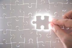 Pezzo del puzzle con incandescenza leggera fotografia stock