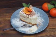 Pezzo della festa di compleanno di Cheescake casalingo con i mandarini su Gray Plate sopra fondo di legno Vista superiore immagini stock libere da diritti
