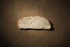 Pezzo della fetta del pane sopra il tessuto della tela da imballaggio, pasto del Cantle sopra il panno di sacco fotografie stock libere da diritti