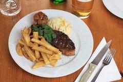 Pezzo di bistecca con le patate fritte, lo slaw delle Cole e l'aglio fritto Immagini Stock